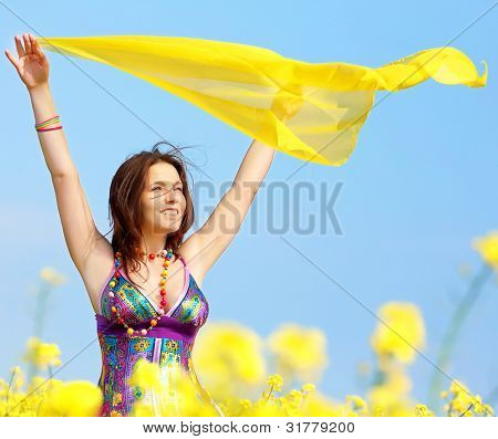 Freedom, young woman with a yellow shawl in rapeseed field