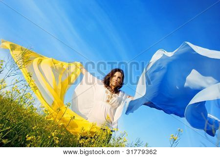 Freedom, young woman with yellow and blue shawl in rapeseed field