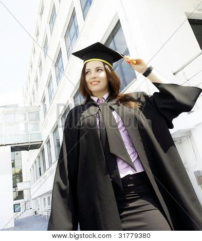 graduation woman portrait smiling and looking happy outdoors