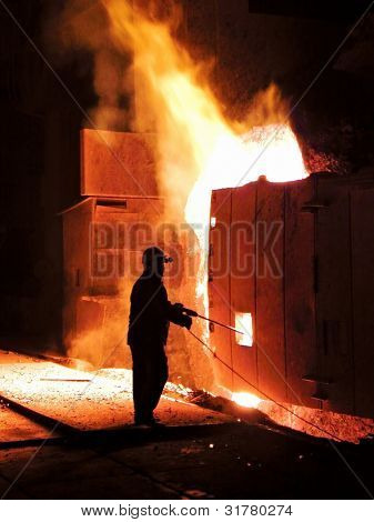 A steel worker takes a sample at steel company