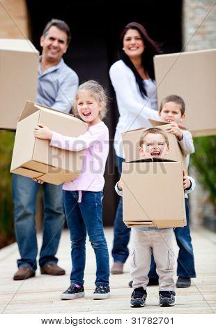 Família movendo casa e carregando caixas de papelão ao ar livre