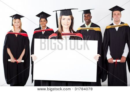 attractive graduate holding white board with classmates in background