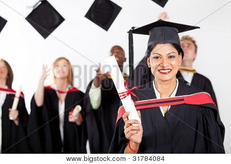 happy female indian graduate at graduation with classmates throwing caps