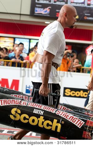 TOA PAYOH, SINGAPORE - MARCH 24 : Contender for Strongman Sulaiman Ismail attempts the 2 times 120 log walk in the Strongman Challenge 2012 on March 24, 2012 in Toa Payoh Hub, Singapore.