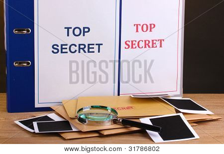 Envelopes and folders with top secret stamp and magnifying glass with photo papers on wooden table on brown background