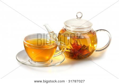 exotic green tea with flowers in glass teapot and cup isolated on white
