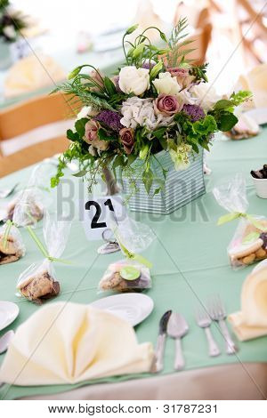 a blue wedding table with cookie favors and flower centerpiece