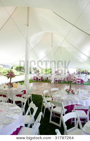 Inside a large wedding tent set up for an outdoor reception
