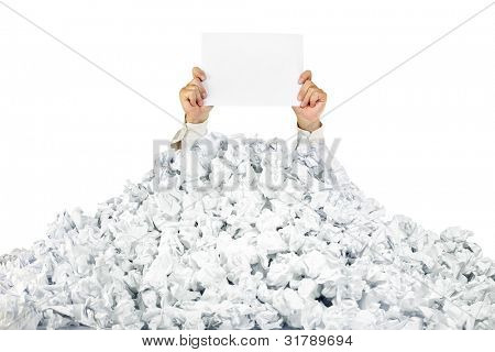 Person under crumpled pile of papers with hand holding a blank page / isolated on white