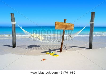 A hanging hammock, a wooden sign post , thongs and starfish on a deserted beach