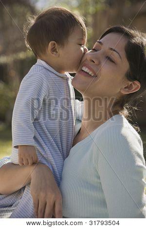 Hispanic baby kissing mother on the cheek