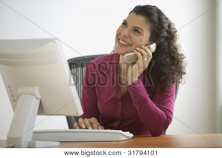 Woman smiling while talking on the phone at desk with computer