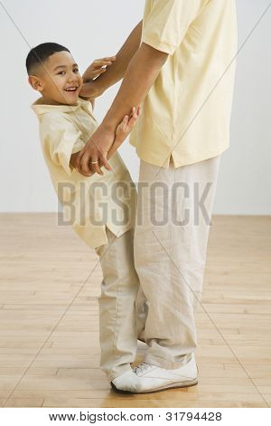 Indian boy standing on father's feet