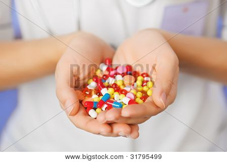 Pills, tablets and drugs heap in doctor's hand on blue background