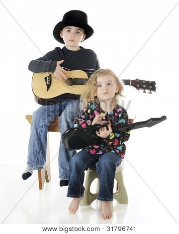 A serious, young elementary boy playing a classical guitar while his preschool sister works on an electric guitar.  On a white background.