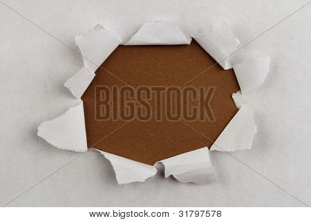 Hole ripped in paper on brown background