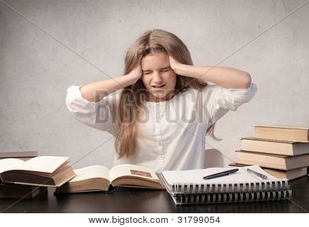 Stressed young student with her head in her hands looking at the bunch of books in front of her
