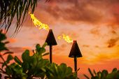 Hawaii luau party Maui fire tiki torches with open flames burning at sunset sky clouds at night. Haw poster