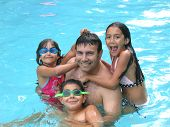 picture of swimming pool family  - Father and three kids having fun in the pool