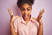 African american woman wearing casual striped shirt standing over isolated pink background very happ poster