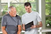 Fitness trainer explaining training plan to senior man in gym