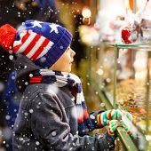 Little Cute Kid Boy Near Sweet Stand With Gingerbread And Nuts. Happy Child On Christmas Market In G poster