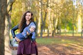 Funny Baby In The Arms Of Mother. Attractive Young Woman Mother With Her Son In Her Arms. Portrait O poster