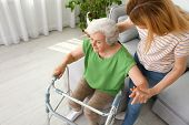 Caretaker Helping Elderly Woman With Walking Frame Indoors poster