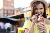 Pretty Young Woman Eating Delicious Sweet Bubble Waffle With Ice Cream Outdoors poster