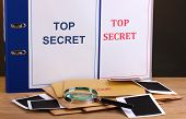 Envelopes and folders with top secret stamp and magnifying glass with photo papers on wooden table o
