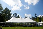 picture of tent  - A large white wedding tent set up for an outdoor function or banquet - JPG
