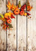 Festive autumn decor from pumpkins, berries and leaves on a rustic wooden background. Concept of Tha poster