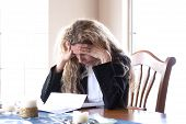 pic of only mature adults  - woman worried about bills and debt and foreclosure - JPG
