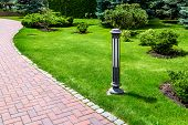 A Garden Ground Lamp Made Of Iron Mounted On A Green Lawn In A Park Near A Stone Walkway For Walks I poster