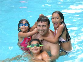 stock photo of swimming pool family  - Father and three kids having fun in the pool