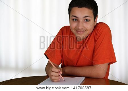 Teen boy doing homework after school at the table