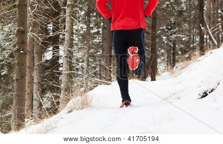Winter trail running: man takes a run on a snowy mountain path in a pine woods.