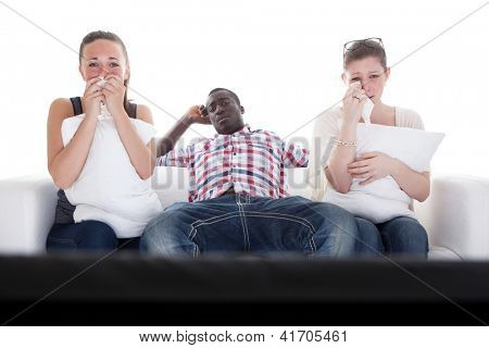 Bored Man And Two Emotional Women Watching Television On Couch