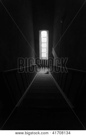 black white scene of downward perspective stairs leading to window