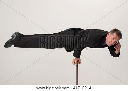 Balancing Businessman Talking On Cell Phone