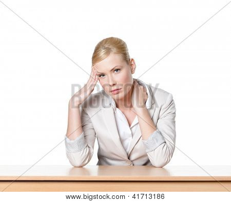 Young business woman sitting at a office desk, isolated