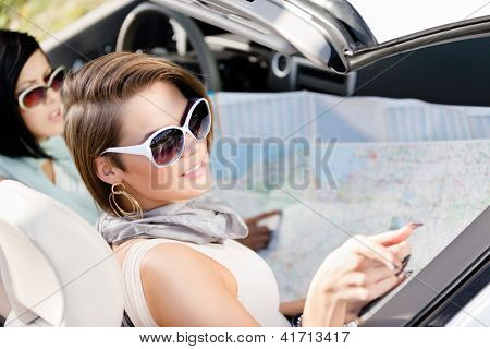 Girls lost their way and check the way with the help of the highway map sitting in the car