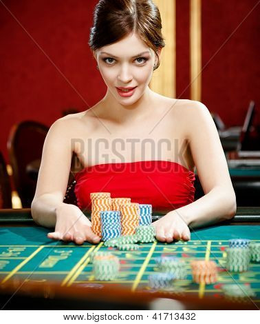 Playing roulette woman places a bet at the casino