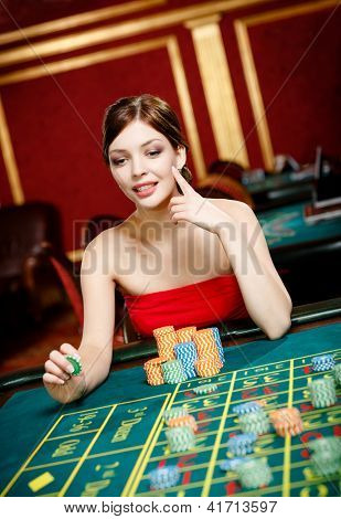 Girl plays at the gambling house. Addiction to the playing roulette