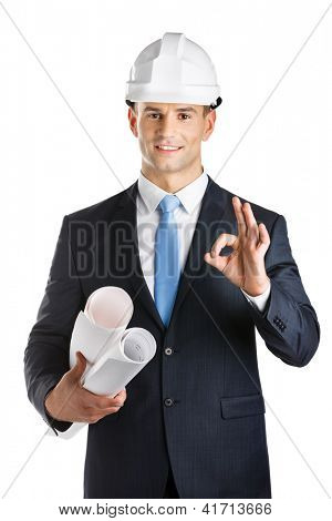 Engineer in hard hat hands blueprints and gestures Okay, isolated on white. Concept of successful construction