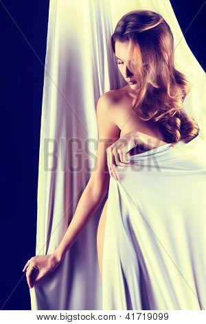 Art portrait of a beautiful naked woman, wrapped in elastic fabric. Black background.