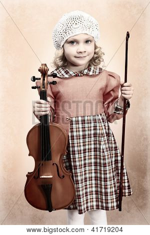 Portrait of a pretty little girl posing with her violin. Vintage style.
