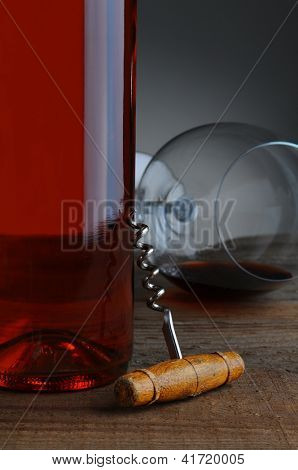 An old fashioned cork screw leaning against a red wine bottle with glass in background.