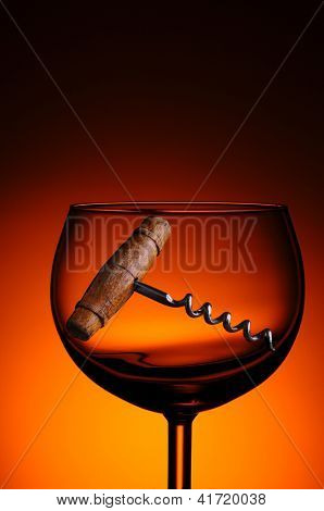 An antique cork screw in a wine glass against a warm light to dark background.