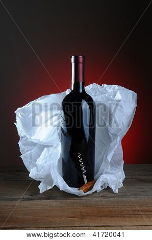Red Wine Bottle and Cork Screw with tissue paper wrapping on wood surface and light to dark background.